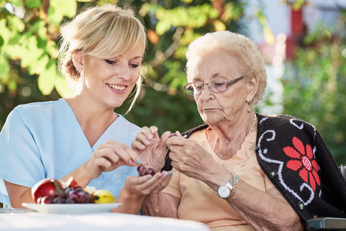 Pflegerin hilft Seniorin beim schlen von Obst
